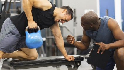 personal trainer training man with heavy kettle bell