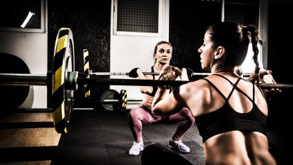 Two young women lifting weights on a cross training in the gym. They are preparing for snatch weightlifting. Young Caucasian women are both in their early thirties.
